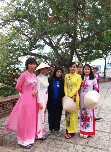 Delegates taking souvenir photo with tour guides wearing ao dai (Vietnamese traditional costume).