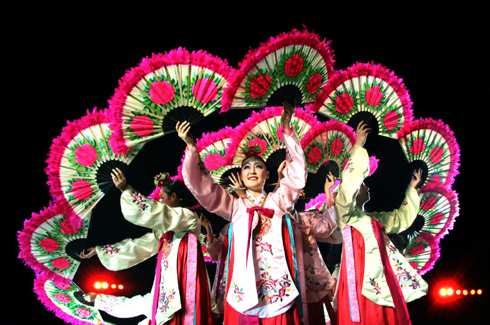 Artists from South Korea performing their traditional dance with fans.