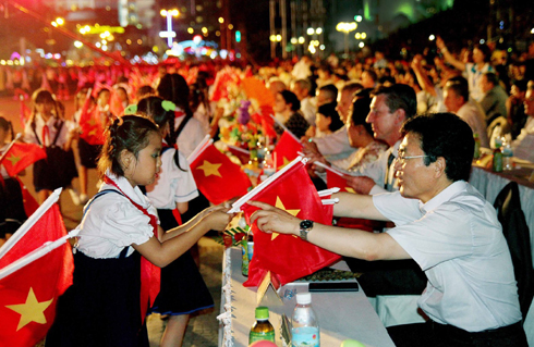 Children in Nha Trang presenting national flags to representatives and tourists in opening night of Sea Festival 2015.
