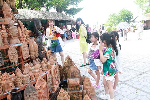 Tourists contemplating pottery products,…