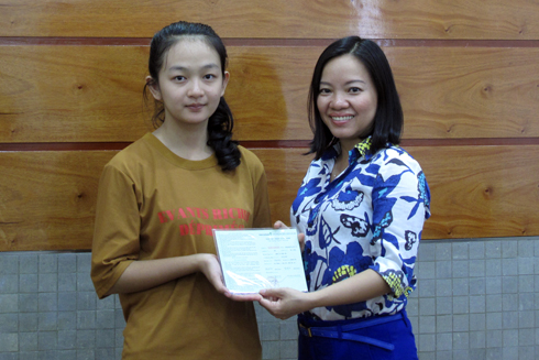 Thai Thi Le Hang, Deputy Editor-in-Chief of Khanh Hoa Newspaper giving passbook to Hang Thi Minh Thu.