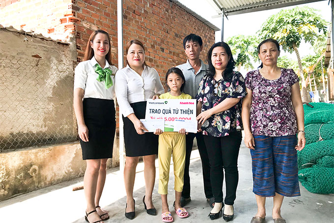 Representatives of Khanh Hoa Newspaper and Vietcombank Nha Trang offering money to siblings' family