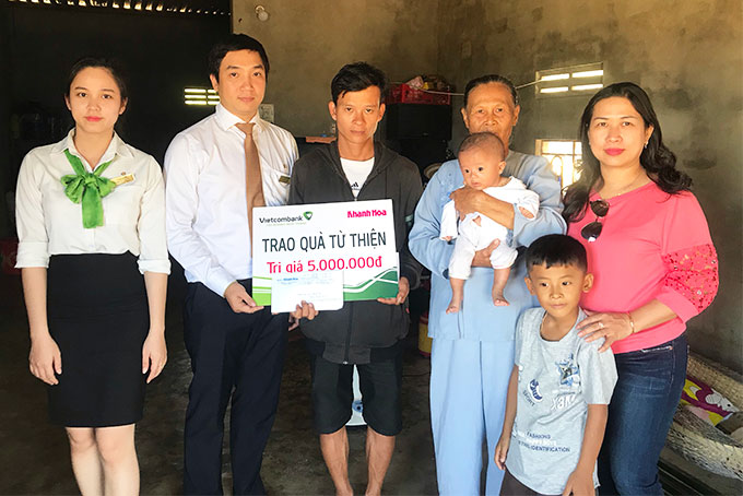 Representatives of Khanh Hoa Newspaper and Vietcombank Nha Trang offering money to the family of the two children.