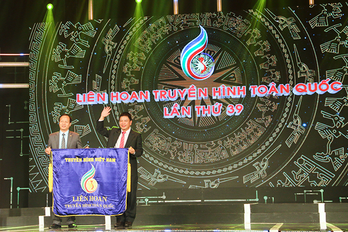 Leader of of Khanh Hoa Radio and Television Station (right) handing over flag to leader of Ninh Binh Province's Radio and Television Station