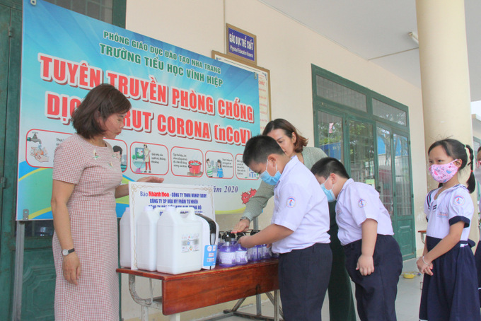 Pupils of Vinh Hiep Primary School washing their hands with gifted sanitizer