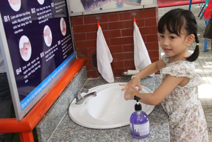 Child at Ly Tu Trong Nursery School washing her hands to prevent COVID-19