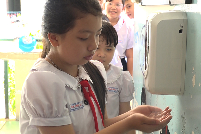Vinh Hai 2 Primary School's pupils washing hands with automatic hand sanitizer dispenser