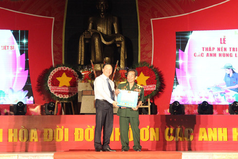 Nguyen Khac Dinh offering gift to Hero of People's Armed Forces Nguyen Duc Quan