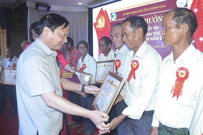 Nguyen Khac Dinh presenting certificates of merit of provincial People's Committee to prestigious people