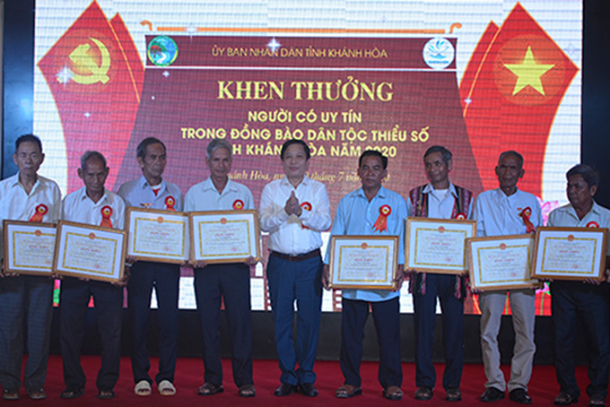 Ha Quoc Tri giving certificates of merit of provincial People's Committee to prestigious people