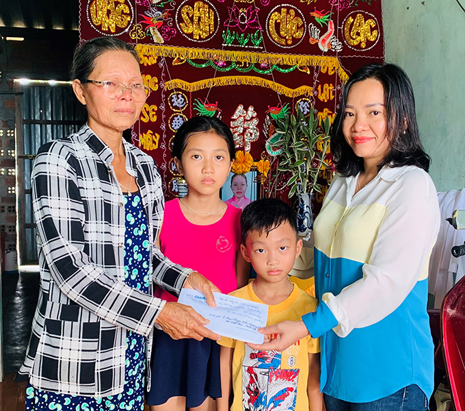 Thai Thi Le Hang—Deputy Editor-in-Chief of Khanh Hoa Newspaper—giving donation from readers to the family of the two orphans.