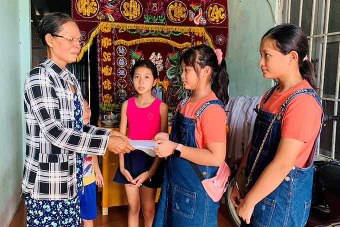 Sisters Nguyen Linh Chi and Nguyen Phuong Khanh (students of Singapore Vietnam International School) offering their piggy bank saving to Ngoc Anh and Hoang Nhan