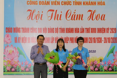 Tran Manh Dung offering flowers to representatives of provincial Labor Union and provincial Labor Union of Officers