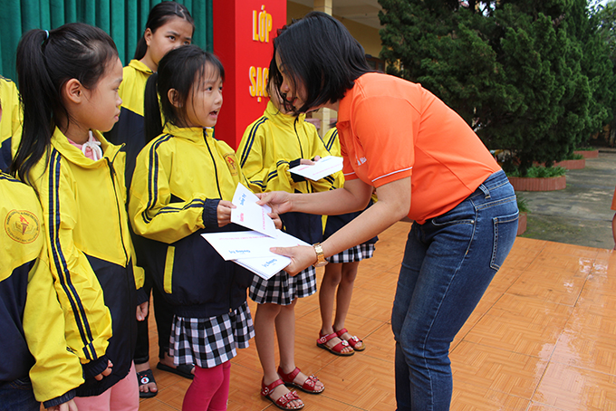 Thai Thi Le Hang presenting support to pupils of Hoa Binh Primary School