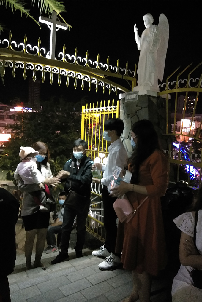 People are given masks and wash their hands with hand sanitizer before entering Nha Trang Cathedral