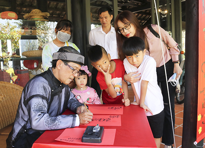 Calligrapher wearing Vietnam's traditional costume offering beautiful writing to visitors