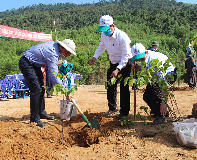Nguyen Khac Dinh (left) plants trees at launching ceremony