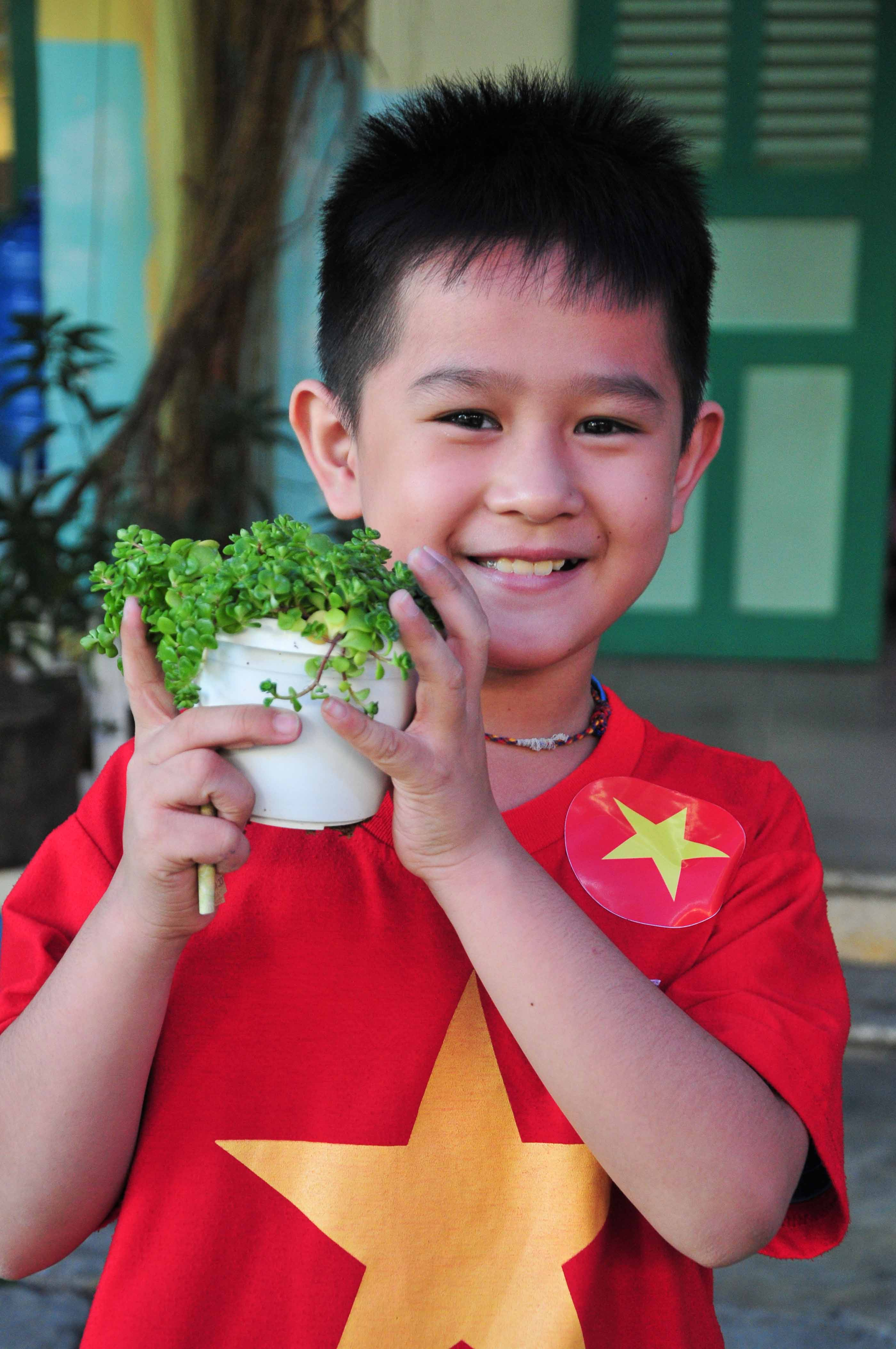 A pupil is happy with his ornamental plant