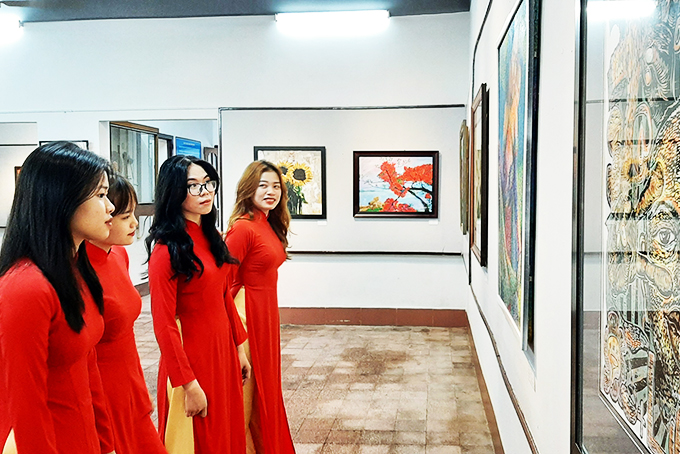 Khanh Hoa University students contemplating exhibited paintings