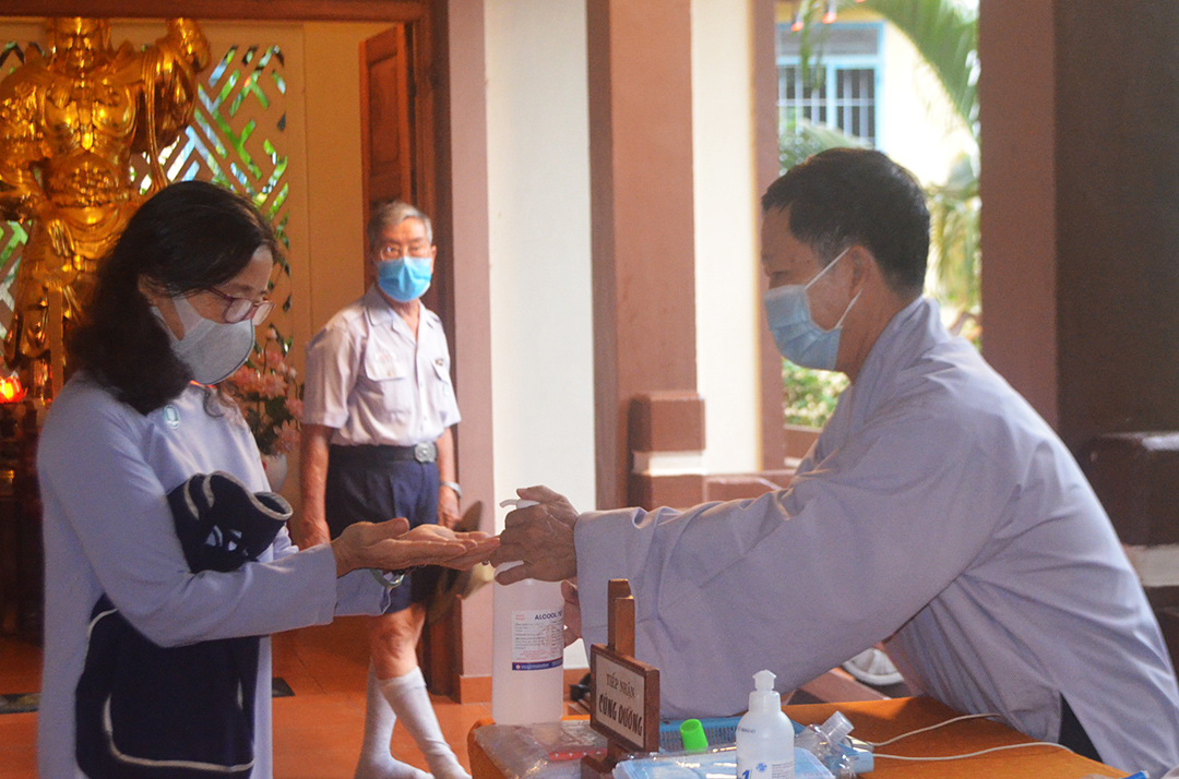 Attendees washing hands with sanitizer and wearing masks