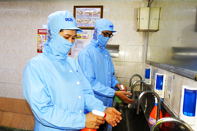 Workers at Khanh Hoa Salangane Nest Company sanitizing their hands before work