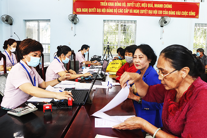 Staff of VBSP doing transactions in Vinh Thanh commune. (Photo taken before March 16, 2021)