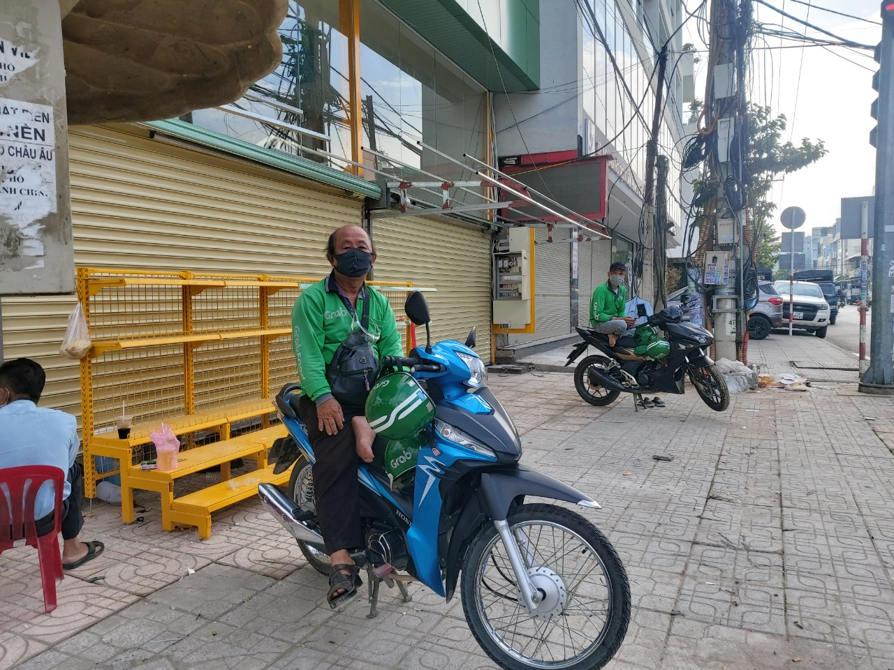Motorbike taxi drivers keep a distance of two meters